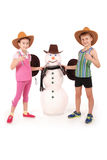 Cute boy and girl holding a cola bottle near a snowman with scarf and hat Stock Photography