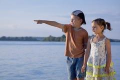 Cute  boy and girl looking at  sea. Cute small boy and girl looking at pretty sea Royalty Free Stock Photo