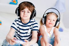 Cute boy and girl playing gaming console Stock Image
