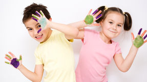 Cute boy and girl playing with paints Stock Photos