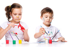 Cute boy and girl playing with paints Stock Image