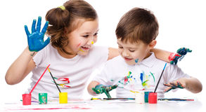 Cute boy and girl playing with paints Royalty Free Stock Photo