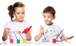 Cute boy and girl playing with paints Stock Photo