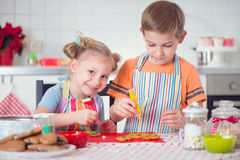 Cute boy and girl preparing Christmas cookies Royalty Free Stock Photography