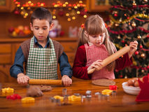 Cute boy and girl preparing Christmas cookies at home Royalty Free Stock Photos