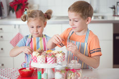 Cute boy and girl preparing Christmas cookies at home Royalty Free Stock Photo