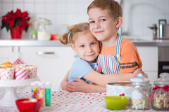 Cute boy and girl preparing Christmas cookies at home Stock Images