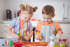 Cute boy and girl preparing Christmas cookies at home Royalty Free Stock Photography