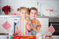 Cute boy and girl preparing Christmas cookies at home Stock Photography