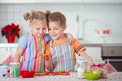 Cute boy and girl preparing Christmas cookies at home Stock Image