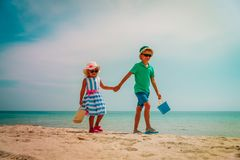 Cute boy and girl walk on tropical beach vacation. Family at sea royalty free stock images