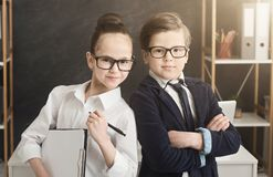 Cute boy and girl working together as team. Family business. Cute boy and girl in formal wear working together as successful team, posing in office, copy space royalty free stock image