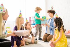Cute boy giving gift boxes to mother at birthday party royalty free stock photos