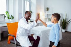 Cute boy giving high five to pleasant professional pediatrician royalty free stock photography