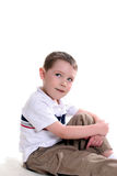 Cute boy glancing sideways. Boy sitting with one knee up and his arms around the knee; looking up and off to the side Stock Photo
