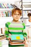 Cute boy with glasses holds books in library Royalty Free Stock Photo