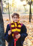 Cute boy in glasses stands in autumn park with gold leaves, holds book in his hands, wears in black robe royalty free stock images