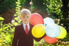 Cute boy going back to school. Boy in the suit. Child with colorful balloons on first school day stock photo