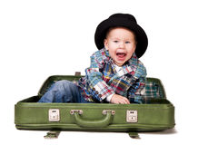 Cute boy in a hat sitting in a suitcase Stock Image