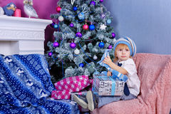 Cute boy in hat unpacking Christmas presents. royalty free stock photo