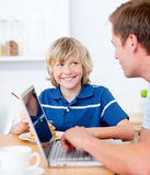Cute boy having breakfast with his father Stock Photos