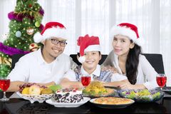 Cute boy having Christmas dinner with his parents. Image of cute little boy with his parents smiling at the camera while having Christmas dinner together at home royalty free stock photos