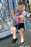 Cute boy having fun on chain swings. Stock Image