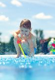 Cute boy having fun, playing near the pool. Cute boy kid having fun, playing near the pool Royalty Free Stock Images