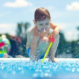 Cute boy having fun, playing near the pool Stock Image