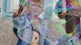 Cute boy having fun playing soap bubbles stock video
