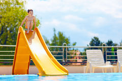 Cute boy having fun on water slide Royalty Free Stock Image