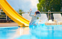Cute boy having fun on water slide Stock Photos