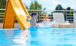 Cute boy having fun on water slide Royalty Free Stock Images