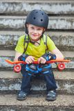 Cute boy in helmet posing with skateboard sitting on steps. Summer outdoor portrait Stock Photography