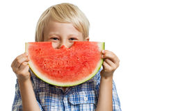 Cute boy hiding behind juciy water melon. A cute happy smiling boy hiding behind a  big juicy slice of watermelon. Isolated on white Royalty Free Stock Photo