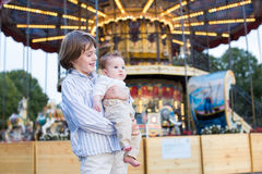Cute boy and his baby sister standing in front of a carousel. Cute boy and his little baby sister standing in front of a carousel Stock Images