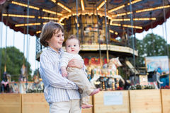 Cute boy and his baby sister standing in front of a carousel. Cute boy and his little baby sister standing in front of a carousel royalty free stock photo