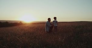 A cute boy with his dad making bubbles in the middle of field, spending good time. Shot on Red Epic stock video footage