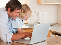Cute boy and his father using a laptop together. In a kitchen royalty free stock images
