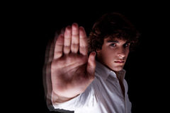 Cute boy with his hand raised in signal to stop Stock Image