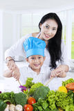 Cute boy and his mom making salad. Photo of a cute boy cooking vegetables salad with her mother in the kitchen at home Royalty Free Stock Image