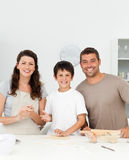 Cute boy with his parents in his kitchen Royalty Free Stock Images
