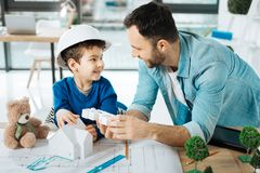 Cute boy and his son discussing 3D house model royalty free stock photos