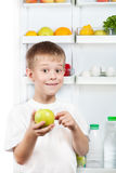 Cute boy is holding an apple near refrigerator Stock Photos