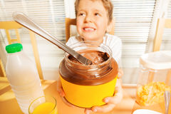 Cute boy holding big can with chocolate spread Royalty Free Stock Images