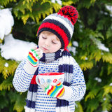 Cute boy holding big cup  and hot chocolate drink and marshmallo Stock Photography