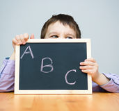 Cute boy is holding blackboard Stock Image