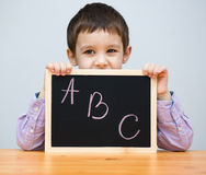 Cute boy is holding blackboard Royalty Free Stock Photography