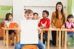 Cute boy holding blank white poster with happy face in kindergarten classroom, kindergarten education concept. stock photography