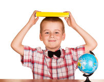 Cute boy holding book over his head, globe isolated. Stock Photography